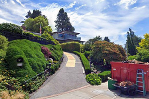 This picture shows our Seattle driveway contractors building a driveway up the hill to a house. Driveway is surrounded by beautiful flowers and bushes