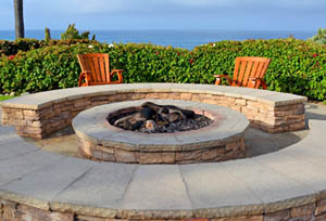 This picture shows a concrete fire pit on a patio